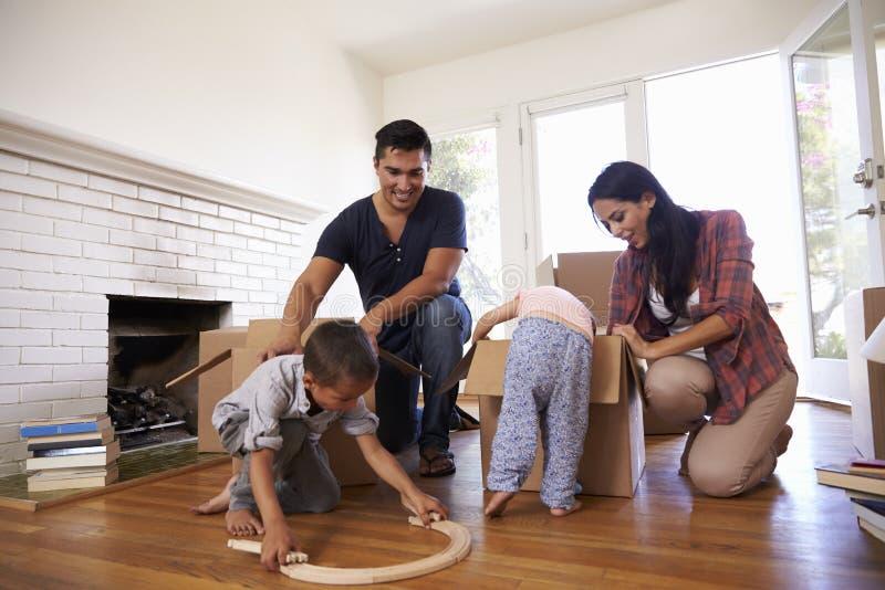 Οικογενειακά ανοίγοντας κιβώτια στο νέο σπίτι στην κίνηση της ημέρας στοκ φωτογραφία με δικαίωμα ελεύθερης χρήσης