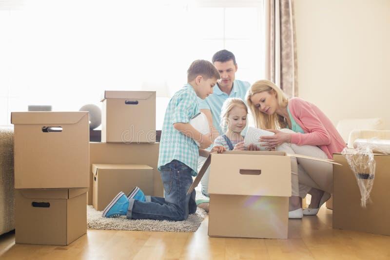 Οικογενειακά ανοίγοντας κουτιά από χαρτόνι στο νέο σπίτι στοκ εικόνες
