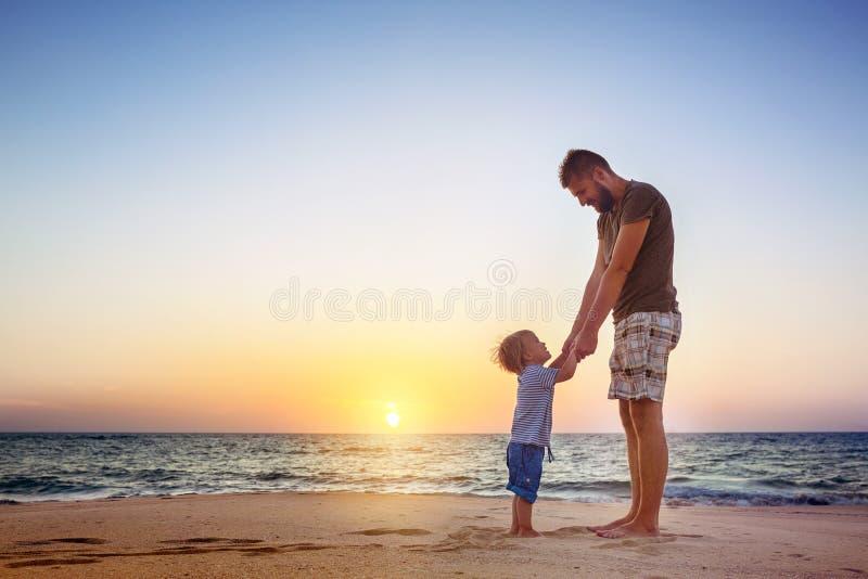 Οικογενειακές διακοπές τροπικών κύκλων παραλιών ηλιοβασιλέματος πατέρων και γιων στοκ εικόνες