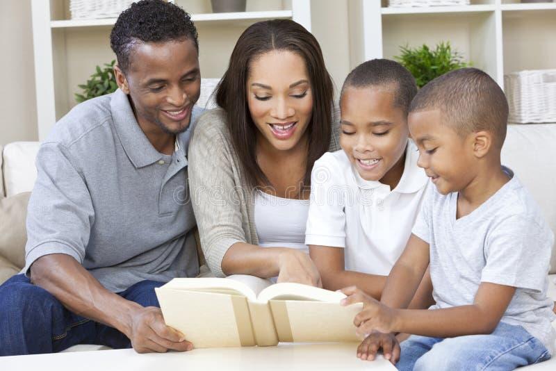Οικογενειακή ανάγνωση πατέρων μητέρων αφροαμερικάνων στοκ φωτογραφία