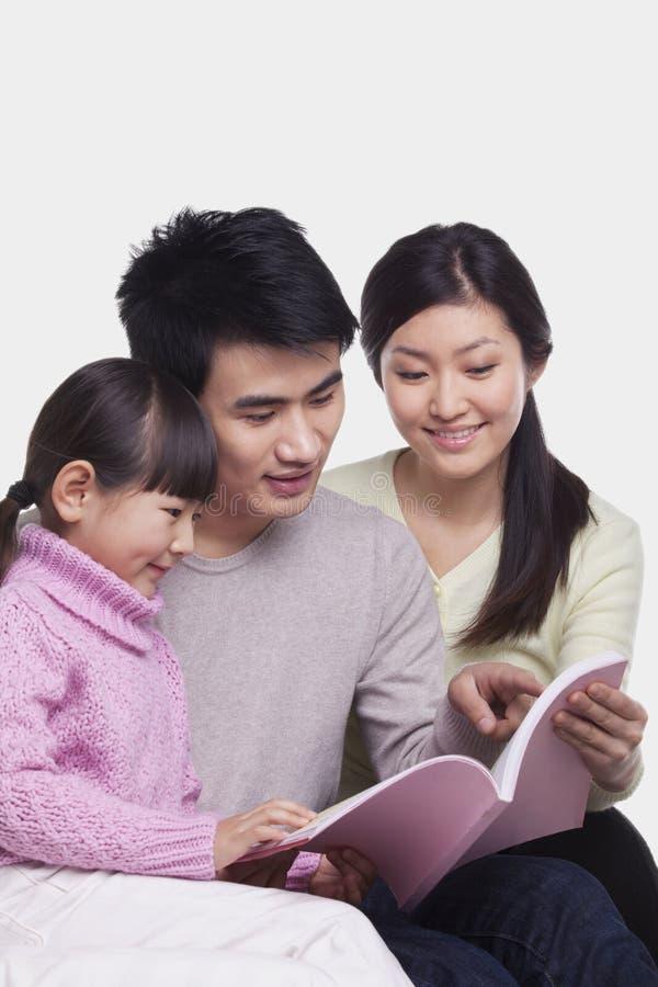 Οικογενειακή ανάγνωση στον καναπέ, πυροβολισμός στούντιο στοκ εικόνες