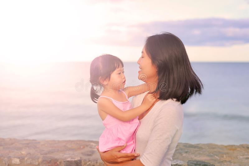 οικογενειακή ευτυχής & Μητέρα και το κορίτσι παιδιών κορών της που παίζουν και που αγκαλιάζουν στο υπόβαθρο θάλασσας στο evenin στοκ εικόνες