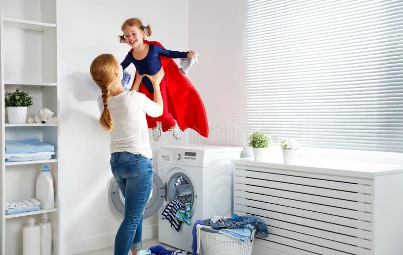 Οικογενειακή μητέρα και κορίτσι παιδιών λίγος αρωγός superhero στο πλυντήριο στοκ εικόνα με δικαίωμα ελεύθερης χρήσης