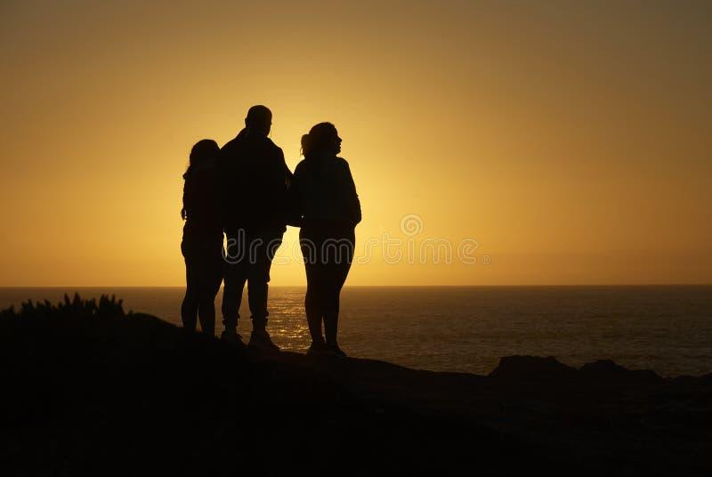 Οικογενειακή σκιαγραφία που αγνοεί τον ωκεανό στοκ εικόνες