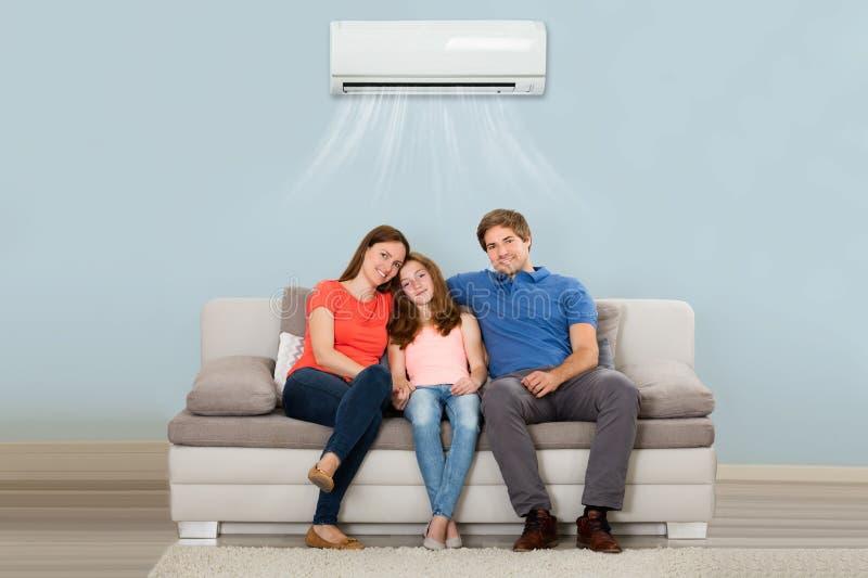 Οικογενειακή συνεδρίαση στον καναπέ κάτω από τον κλιματισμό στοκ εικόνες
