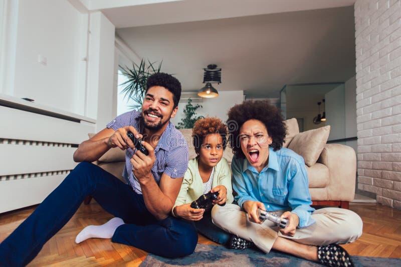 Οικογενειακή συνεδρίαση στον καναπέ που παίζει μαζί τα τηλεοπτικά παιχνίδια, εκλεκτική εστίαση στοκ εικόνα