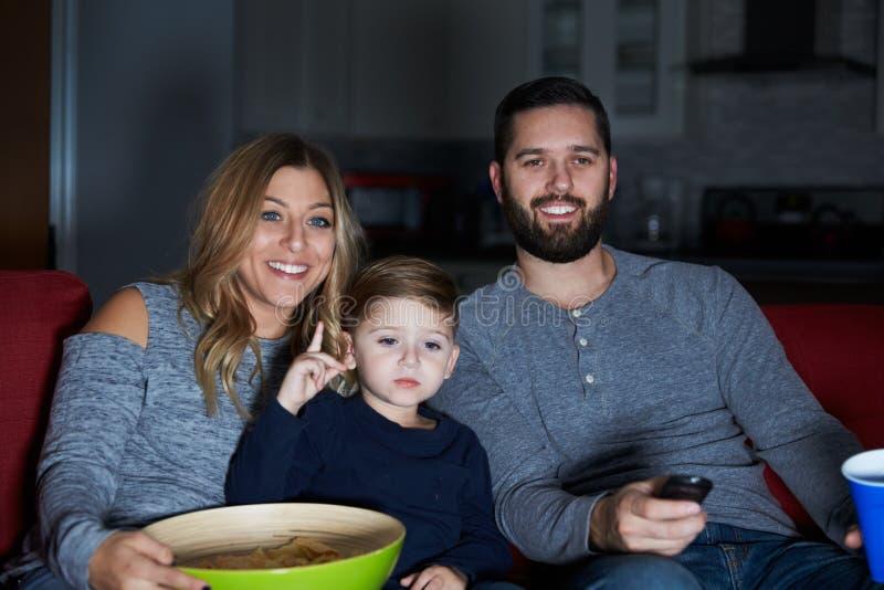 Οικογενειακή συνεδρίαση στην τηλεόραση προσοχής καναπέδων από κοινού στοκ εικόνα με δικαίωμα ελεύθερης χρήσης