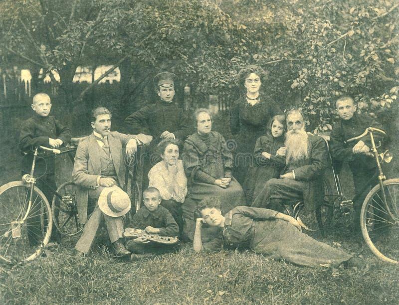 Οικογενειακή φωτογραφία, οικογένεια και εννέα παιδιά που θέτουν στο υπόβαθρο του κήπου με το xylophone δύο ποδηλάτων στοκ φωτογραφίες με δικαίωμα ελεύθερης χρήσης