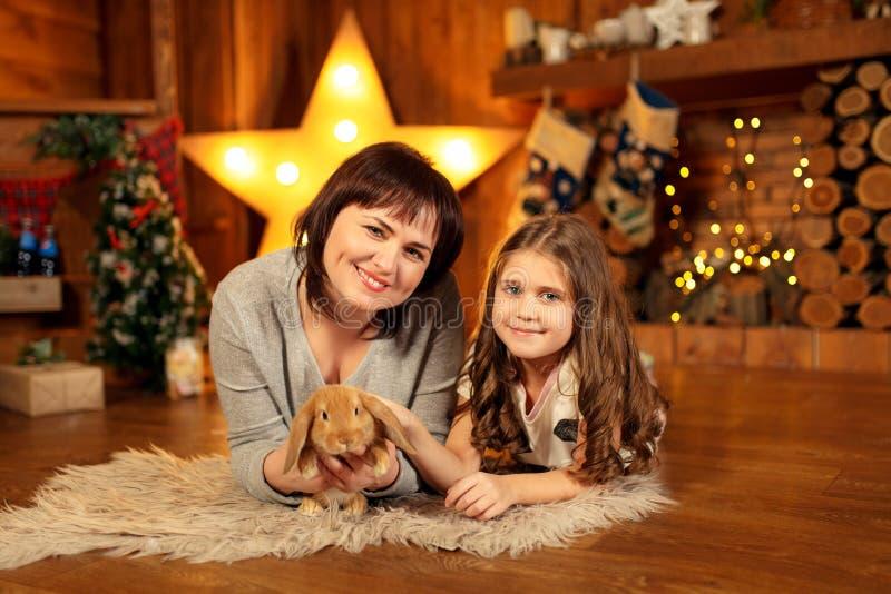 Οικογενειακή φωτογραφία της μητέρας και της κόρης που βάζουν στο πάτωμα στην εστία με το χαριτωμένο κουνέλι τα Χριστούγεννα διακο στοκ φωτογραφίες