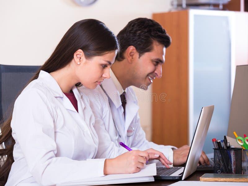 Οικογενειακοί γιατροί με την εργασία στηθοσκοπίων στην αρχή από κοινού στοκ φωτογραφίες