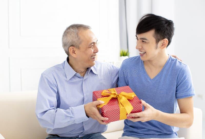 οικογενειακοί εορτασμός και γιος που δίνουν το δώρο στον πατέρα στοκ φωτογραφίες