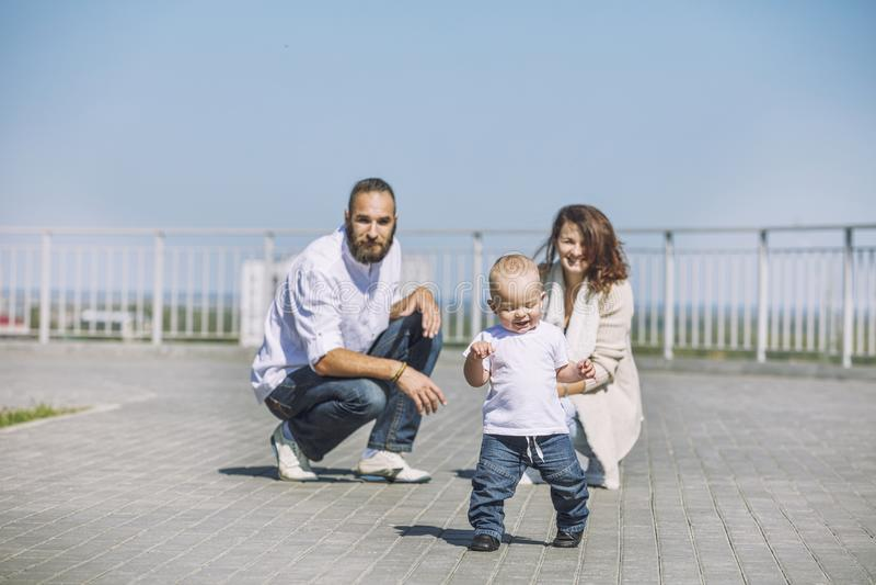 Οικογενειακοί mom μπαμπάς και μωρό ευχαριστημένοι από τα χαμόγελα μαζί στο πάρκο ο στοκ φωτογραφίες