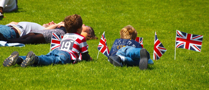 Οικογενειακός εορτασμός με τα Union Jack που πετούν την τοποθέτηση στη χλόη στοκ φωτογραφία με δικαίωμα ελεύθερης χρήσης