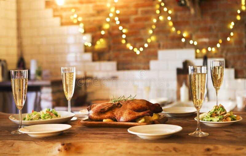 Οικογενειακό γεύμα διακοπών με τα πουλερικά και τη σαμπάνια ψητού στοκ φωτογραφίες