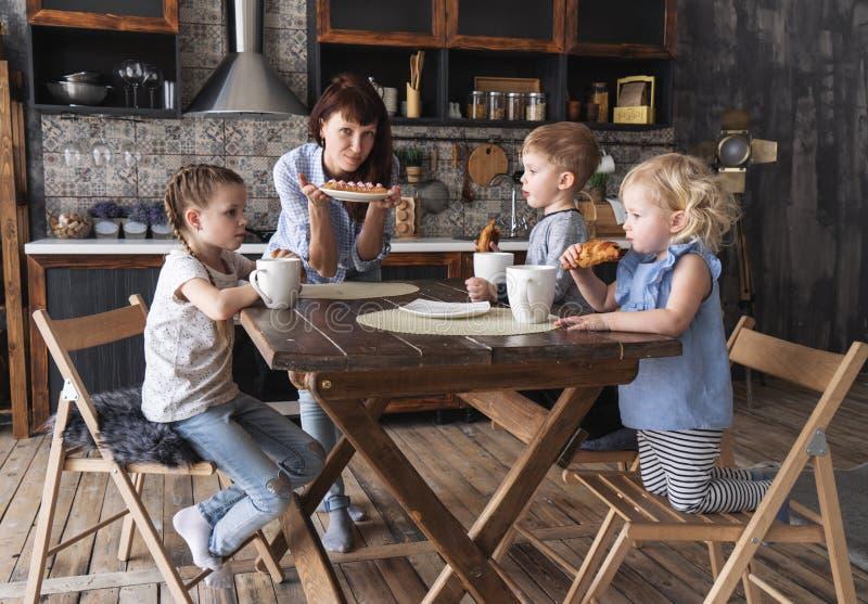 Οικογενειακό γεύμα: Τα παιδιά πίνουν το τσάι και η μητέρα φέρνει ένα πιάτο κέικ στον πίνακα στοκ εικόνες