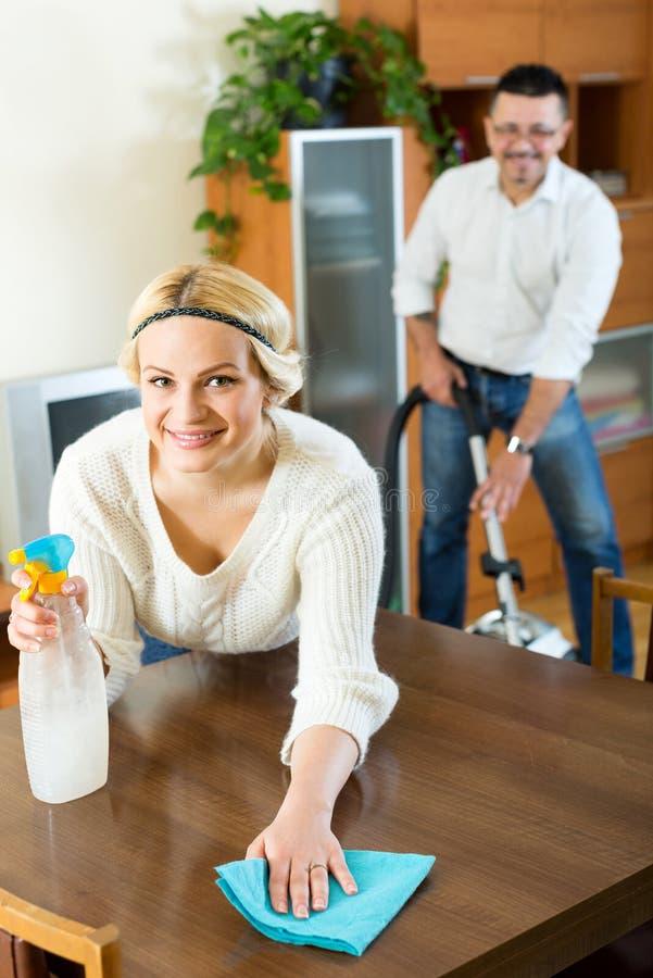 Οικογενειακό ζεύγος που καθαρίζει στο σπίτι στοκ φωτογραφία με δικαίωμα ελεύθερης χρήσης