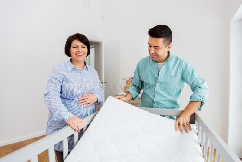 Οικογενειακό ζεύγος που τακτοποιεί το κρεβάτι μωρών με το στρώμα στοκ φωτογραφίες