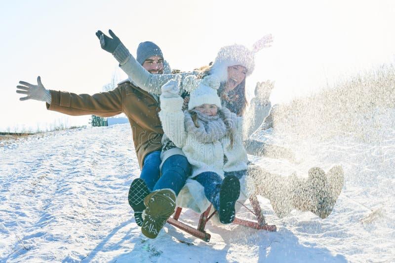 Οικογενειακό οδηγώντας έλκηθρο στο χιόνι στοκ εικόνα