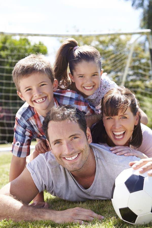 Οικογενειακό παίζοντας ποδόσφαιρο στον κήπο από κοινού στοκ εικόνα