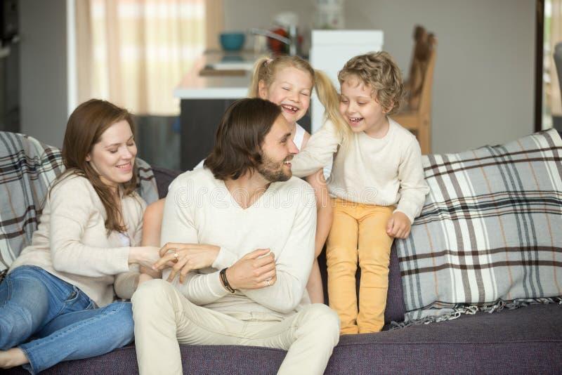 Οικογενειακό παιχνίδι με τα παιδιά που γελούν έχοντας τη συνεδρίαση διασκέδασης στον καναπέ στοκ εικόνες