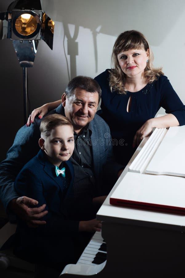 Οικογενειακό παιχνίδι στο πιάνο Ο πατέρας και η μητέρα διδάσκουν το γιο για να παίξουν ένα μουσικό όργανο στοκ φωτογραφία με δικαίωμα ελεύθερης χρήσης