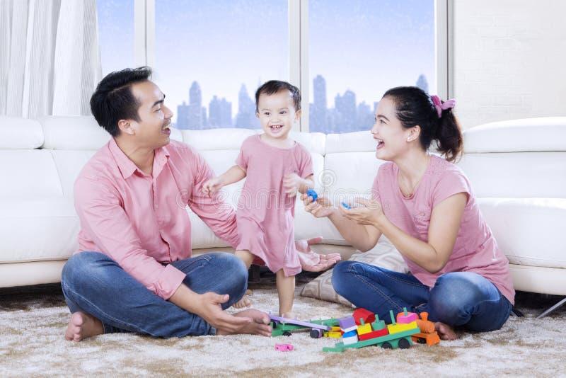 Οικογενειακό παιχνίδι με τα παιχνίδια στον τάπητα στοκ φωτογραφία