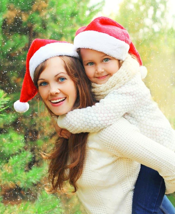 Οικογενειακό παιδί Χριστουγέννων που αγκαλιάζει τη μητέρα στα κόκκινα καπέλα santa μαζί πέρα από το δέντρο που έχει τη διασκέδαση στοκ εικόνα