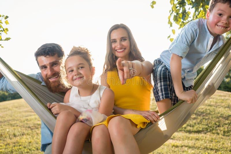 Οικογενειακό πορτρέτο με την όμορφη μητέρα δύο παιδιών δίπλα στο σύζυγό της στοκ εικόνα