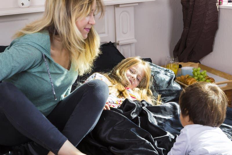 Οικογενειακό πορτρέτο στο κρεβάτι στο σπίτι στοκ φωτογραφίες