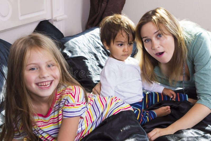 Οικογενειακό πορτρέτο στο κρεβάτι στο σπίτι στοκ φωτογραφία με δικαίωμα ελεύθερης χρήσης