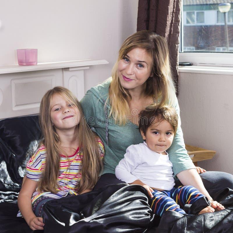 Οικογενειακό πορτρέτο στο κρεβάτι στο σπίτι στοκ εικόνες με δικαίωμα ελεύθερης χρήσης