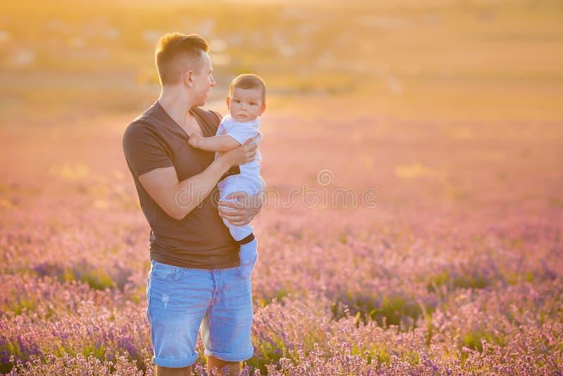 Οικογενειακό πορτρέτο της τοποθέτησης γιων μωρών εκμετάλλευσης πατέρων lavender στον τομέα που φορά το τζιν παντελόνι και την μπλ στοκ εικόνες