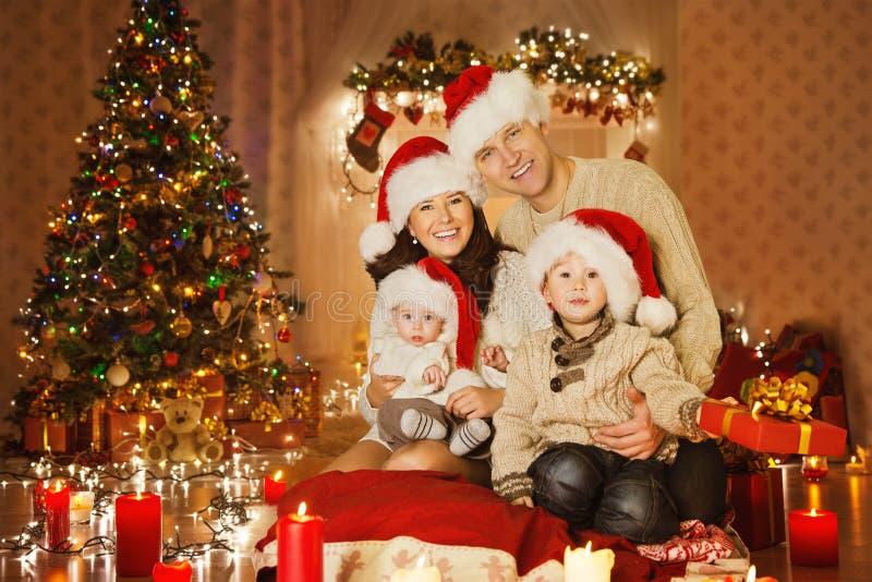Οικογενειακό πορτρέτο Χριστουγέννων στο δωμάτιο εγχώριων διακοπών, στο καπέλο Santa στοκ εικόνες