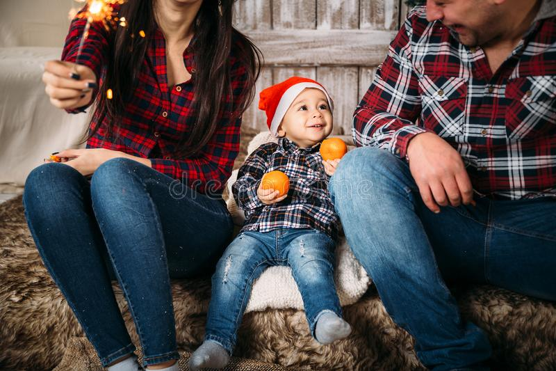Οικογενειακό πορτρέτο Χριστουγέννων του παιδάκι στο κόκκινο καπέλο santa με τα πορτοκάλια στα χέρια που κάθονται μεταξύ των γονέω στοκ φωτογραφία με δικαίωμα ελεύθερης χρήσης