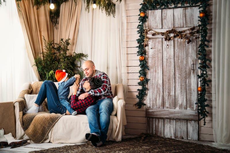 Οικογενειακό πορτρέτο Χριστουγέννων των νέων ευτυχών χαμογελώντας γονέων που παίζουν με το μικρό παιδί στο κόκκινο καπέλο santa Χ στοκ εικόνες με δικαίωμα ελεύθερης χρήσης