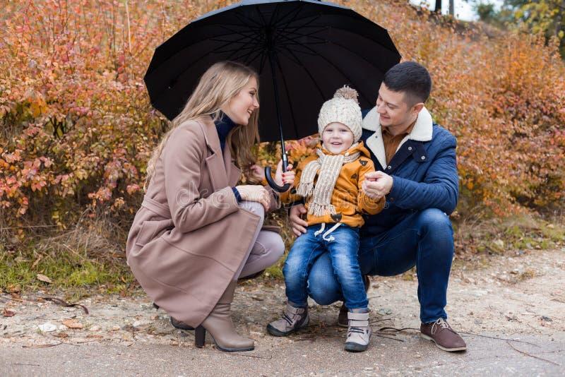 Οικογενειακό φθινόπωρο στο πάρκο στην ομπρέλα βροχής στοκ φωτογραφία