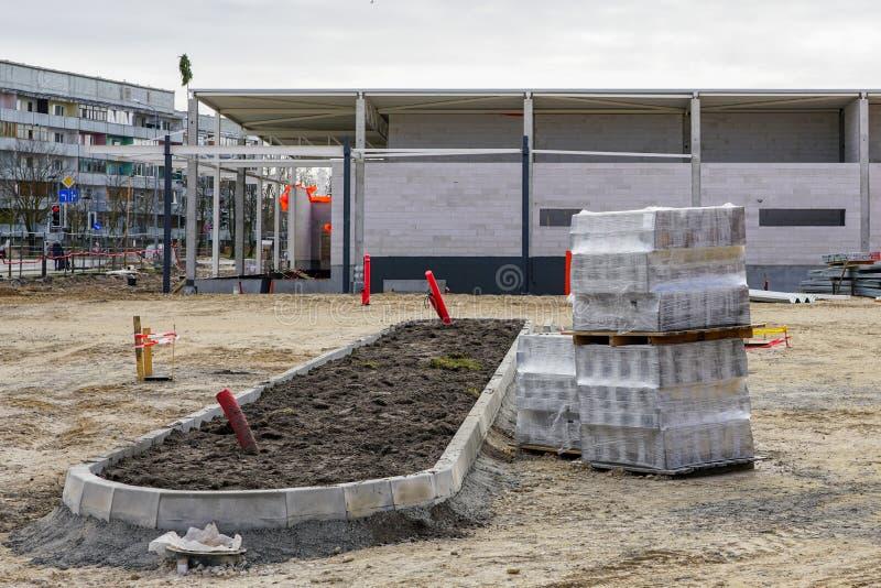 Οικοδόμηση ενός υπαίθριου σταθμού αυτοκινήτων κοντά στη νέα οικοδόμηση του καταστήματος στοκ φωτογραφία με δικαίωμα ελεύθερης χρήσης