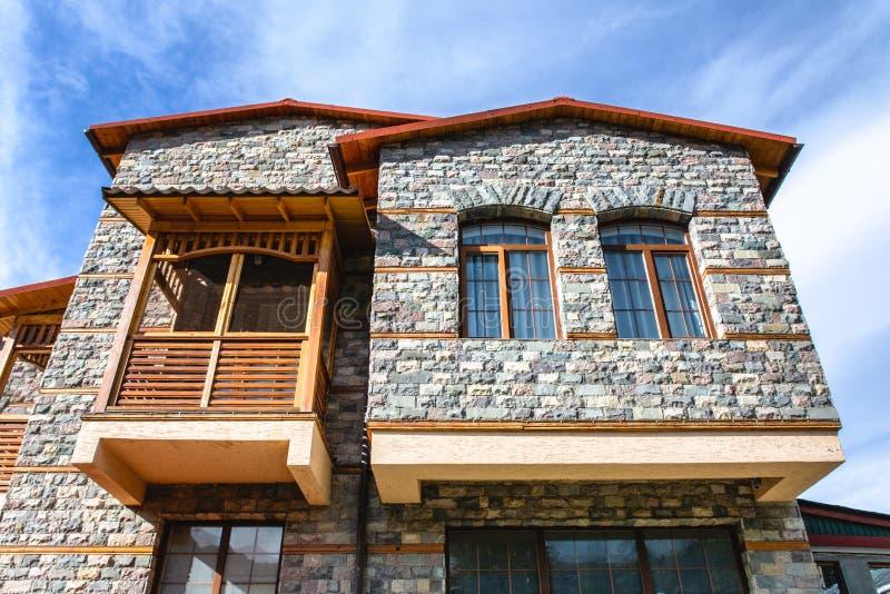 Οικοδόμηση με μια πρόσοψη πετρών και ένα όμορφο ξύλινο μπαλκόνι στοκ εικόνες
