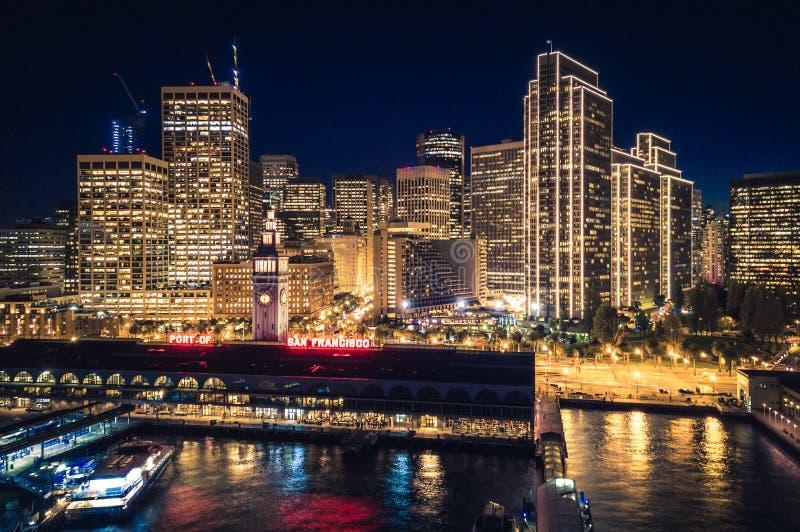 Οικοδόμηση οριζόντων και πορθμείων του Σαν Φρανσίσκο τη νύχτα με τις διακοπές στοκ φωτογραφία