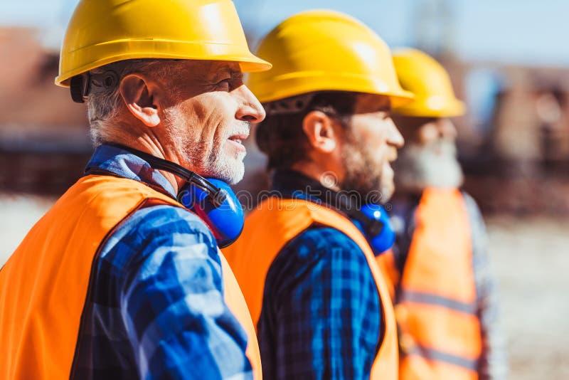 Οικοδόμοι στις αντανακλαστικές φανέλλες και hardhats που στέκονται μαζί στο εργοτάξιο οικοδομής, κοίταγμα στοκ εικόνες