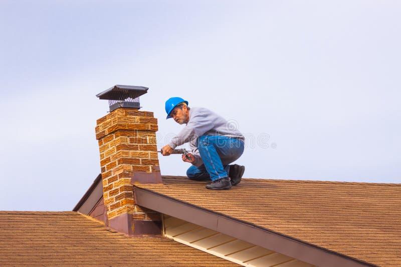 Οικοδόμος αναδόχου στη στέγη με την μπλε hardhat καλαφατίζοντας καπνοδόχο στοκ εικόνα