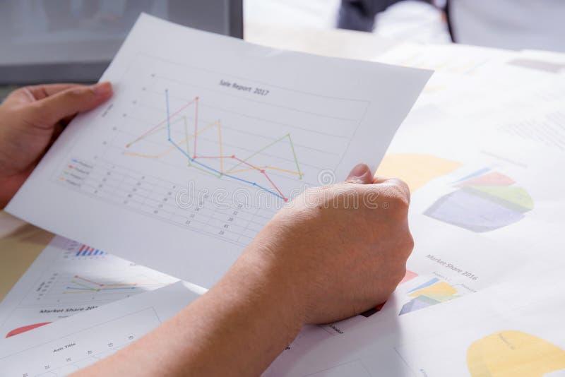 Οικονομικά διαγράμματα εγγράφου με το χέρι, τις γραφικές παραστάσεις και το σημειωματάριο λαβής στοκ εικόνες