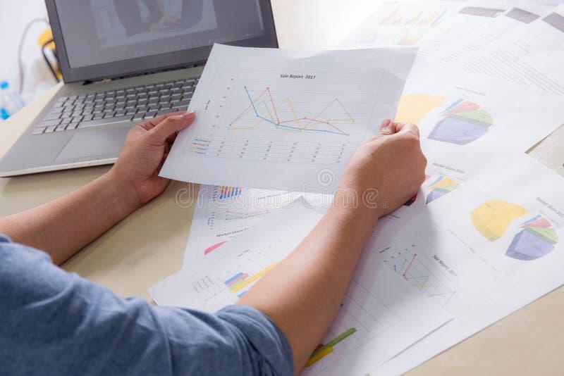 Οικονομικά διαγράμματα εγγράφου με το χέρι, τις γραφικές παραστάσεις και το σημειωματάριο λαβής στον πίνακα στοκ εικόνα