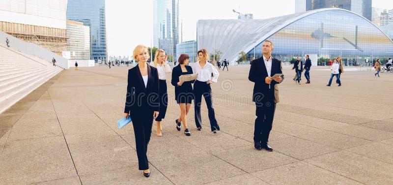 Οικονομικά μέλη ομάδας που περνούν με την ταμπλέτα, τις περιπτώσεις και την εξέταση στοκ εικόνες