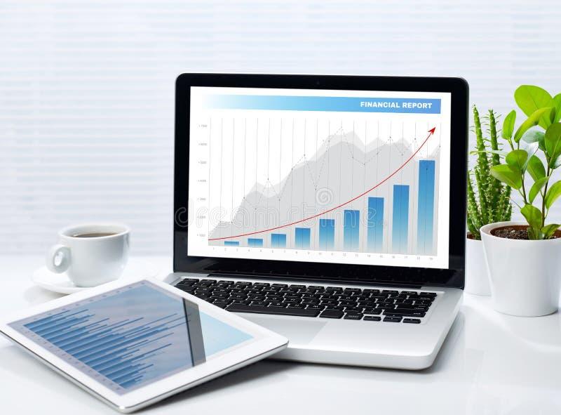 Οικονομικές γραφικές παραστάσεις στο lap-top και την ταμπλέτα στοκ εικόνες