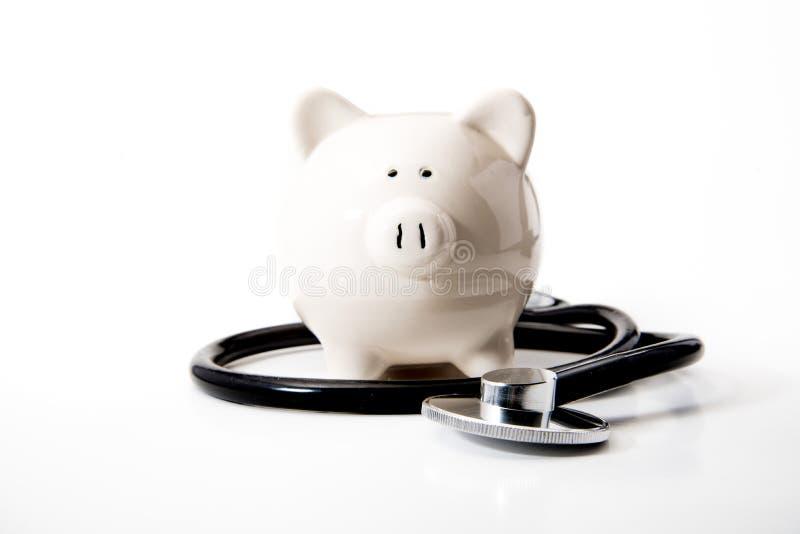 Οικονομική υγεία - μαύρες στηθοσκόπιο & τράπεζα Piggy στοκ εικόνες
