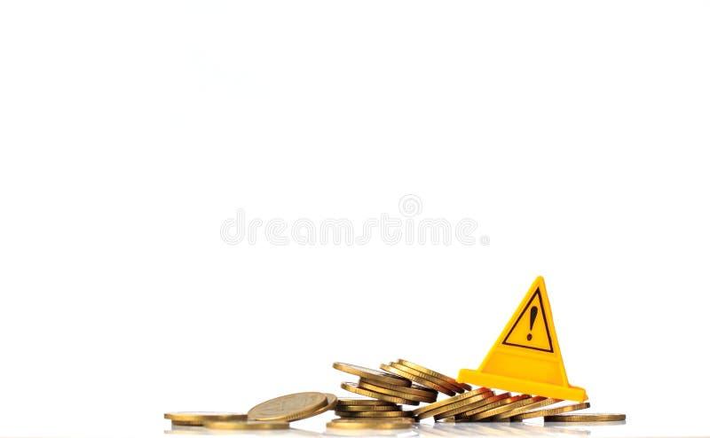 οικονομικός κίνδυνος Νομίσματα που πέφτουν και ετικέτα προειδοποίησης στοκ φωτογραφίες με δικαίωμα ελεύθερης χρήσης