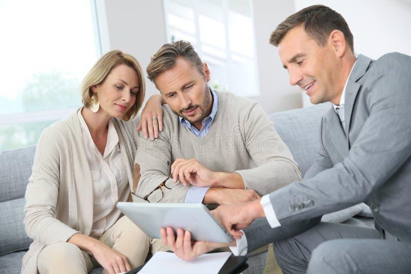 Οικονομικός σύμβουλος με το ζεύγος της συζήτησης πελατών στοκ φωτογραφία