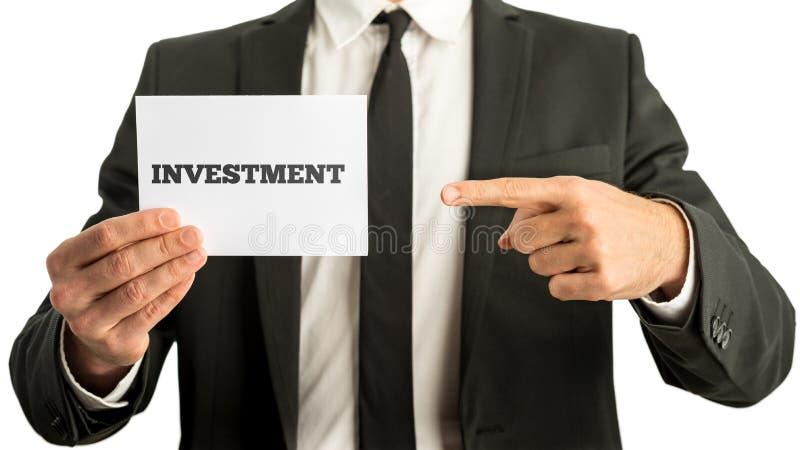 Οικονομικός σύμβουλος που κρατά ψηλά μια άσπρη κάρτα με το σημάδι επένδυσης στοκ εικόνες