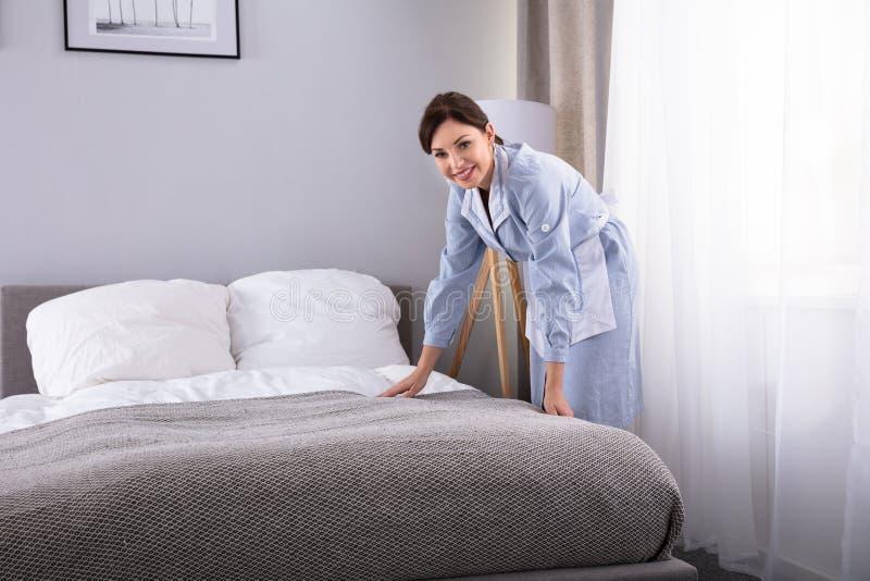 Οικονόμος που κάνει το κρεβάτι στο δωμάτιο ξενοδοχείου στοκ εικόνες